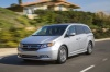 Driving 2014 Honda Odyssey Touring Elite in Alabaster Silver Metallic from a front left three-quarter view