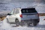Picture of a driving 2020 Honda Passport Elite AWD in Lunar Silver Metallic from a rear left perspective