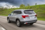 Picture of a driving 2016 Honda Pilot AWD in Lunar Silver Metallic from a rear left three-quarter perspective