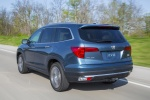 Picture of a driving 2016 Honda Pilot AWD in Steel Sapphire Metallic from a rear left perspective