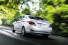 Driving 2013 Hyundai Accent GLS Sedan in Ironman Silver from a rear left view