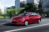 Driving 2013 Hyundai Accent GLS Sedan in Boston Red from a front left three-quarter view