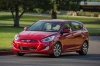 Driving 2015 Hyundai Accent Hatchback in Boston Red Metallic from a front left view