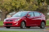 Driving 2015 Hyundai Accent Hatchback in Boston Red Metallic from a front left three-quarter view