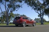 Driving 2013 Hyundai Santa Fe in Regal Red Pearl from a rear right three-quarter view