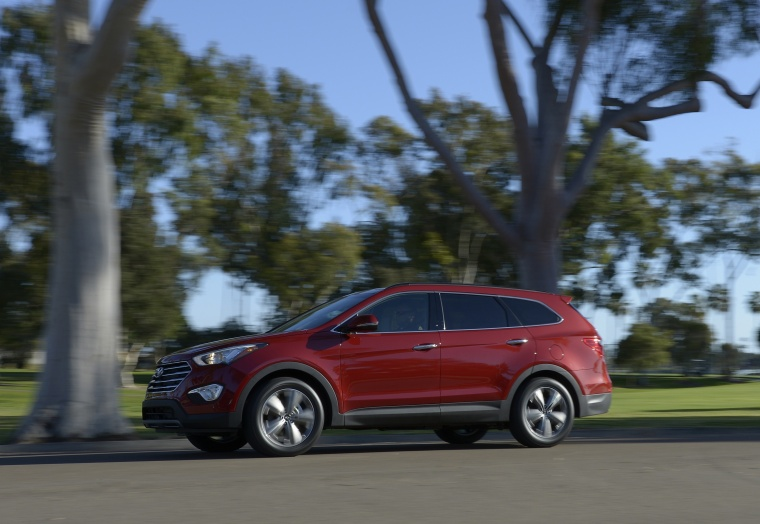 Driving 2016 Hyundai Santa Fe in Regal Red Pearl from a left side view