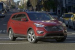 Picture of a driving 2016 Hyundai Santa Fe in Regal Red Pearl from a front right perspective