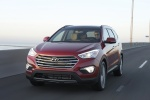 Picture of a driving 2016 Hyundai Santa Fe in Regal Red Pearl from a front left perspective