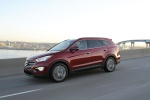 Picture of a driving 2016 Hyundai Santa Fe in Regal Red Pearl from a front left three-quarter perspective