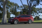Picture of a driving 2016 Hyundai Santa Fe in Regal Red Pearl from a left side perspective