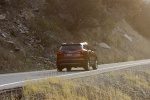Picture of a driving 2016 Hyundai Santa Fe Sport in Serrano Red from a rear right perspective