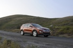 Picture of a driving 2016 Hyundai Santa Fe Sport in Serrano Red from a front right three-quarter perspective