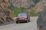 Picture of a driving 2016 Hyundai Santa Fe Sport in Serrano Red from a front left perspective