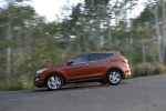 Picture of a driving 2016 Hyundai Santa Fe Sport in Serrano Red from a left side perspective