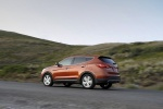 Picture of a driving 2016 Hyundai Santa Fe Sport in Serrano Red from a rear left three-quarter perspective