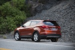 Picture of a driving 2016 Hyundai Santa Fe Sport in Serrano Red from a rear left perspective
