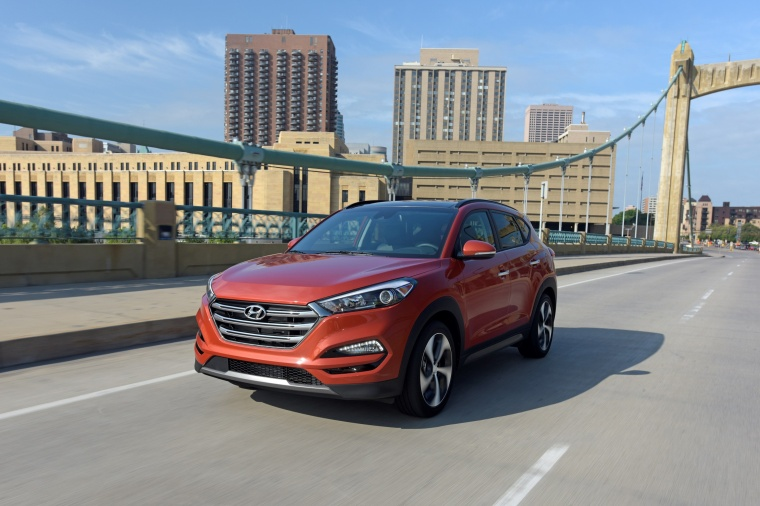 Picture of a driving 2016 Hyundai Tucson Limited 1.6T AWD in Sedona Sunset from a front left perspective