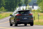 Picture of a driving 2016 Hyundai Tucson Limited 1.6T in Coliseum Gray from a rear left perspective