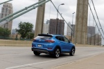 Picture of a driving 2016 Hyundai Tucson Limited 1.6T AWD in Caribbean Blue from a rear right three-quarter perspective