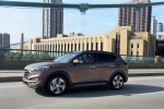 Picture of a driving 2016 Hyundai Tucson Limited 1.6T AWD in Mojave Sand from a front left three-quarter perspective