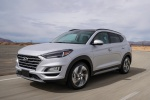 Picture of a driving 2019 Hyundai Tucson in Molten Silver from a front left three-quarter perspective