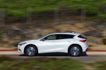 Picture of a driving 2019 Infiniti QX30 in Majestic White from a side perspective