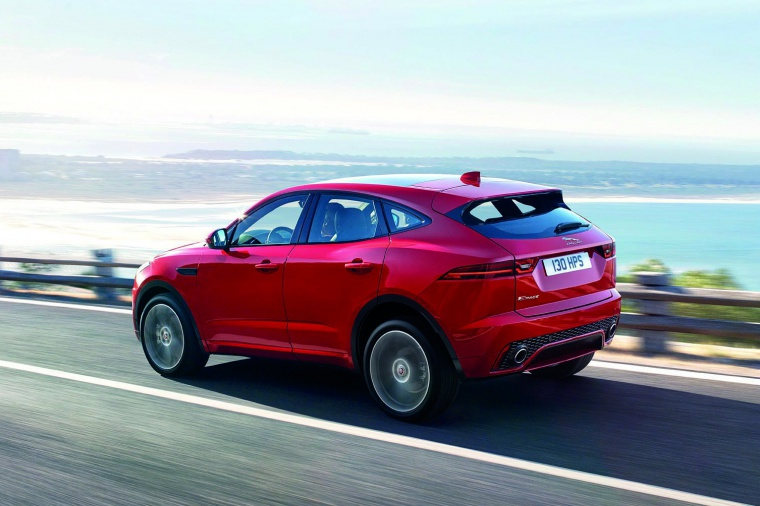 Driving 2020 Jaguar E-Pace P300 R-Dynamic AWD in Firenze Red Metallic from a rear left three-quarter view