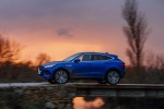 Picture of a driving 2020 Jaguar E-Pace P300 R-Dynamic AWD in Caesium Blue Metallic from a side perspective