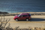 Picture of a driving 2015 Jeep Cherokee Latitude in Deep Cherry Red Crystal Pearlcoat from a side perspective
