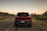 Picture of a driving 2015 Jeep Cherokee Limited 4WD in Deep Cherry Red Crystal Pearlcoat from a rear perspective