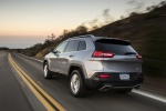 Picture of a driving 2015 Jeep Cherokee Limited 4WD in Billet Silver Metallic Clearcoat from a rear left three-quarter perspective