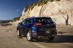 Picture of a driving 2015 Jeep Cherokee Limited 4WD in True Blue Pearlcoat from a rear left perspective