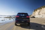 Picture of a driving 2015 Jeep Cherokee Limited 4WD in True Blue Pearlcoat from a rear perspective