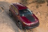 Picture of a driving 2016 Jeep Cherokee Trailhawk 4WD in Deep Cherry Red Crystal Pearlcoat from a front right perspective