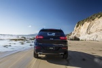 Picture of a driving 2016 Jeep Cherokee Limited 4WD in True Blue Pearlcoat from a rear perspective