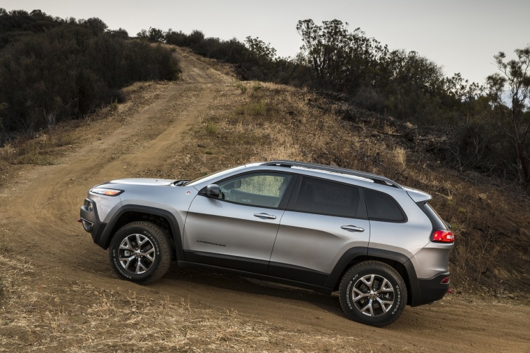 Picture of a driving 2017 Jeep Cherokee Trailhawk 4WD in Billet Silver Metallic Clearcoat from a side perspective