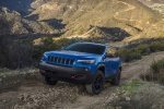 Picture of a driving 2019 Jeep Cherokee Trailhawk 4WD in Hydro Blue Pearlcoat from a front left perspective