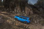 Picture of a driving 2019 Jeep Cherokee Trailhawk 4WD in Hydro Blue Pearlcoat from a rear left three-quarter perspective