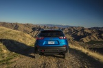 Picture of a driving 2019 Jeep Cherokee Trailhawk 4WD in Hydro Blue Pearlcoat from a rear perspective