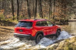 Picture of a driving 2019 Jeep Cherokee Trailhawk 4WD in Firecracker Red Clearcoat from a rear right three-quarter perspective