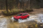 Picture of a driving 2019 Jeep Cherokee Trailhawk 4WD in Firecracker Red Clearcoat from a front left three-quarter perspective