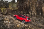 Picture of a driving 2019 Jeep Cherokee Trailhawk 4WD in Firecracker Red Clearcoat from a rear left three-quarter perspective