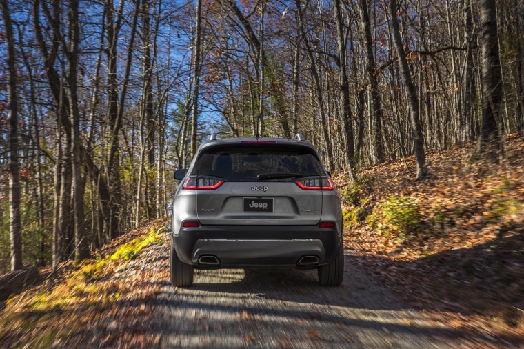 Picture of a driving 2020 Jeep Cherokee Limited 4WD in Billet Silver Metallic Clearcoat from a rear perspective