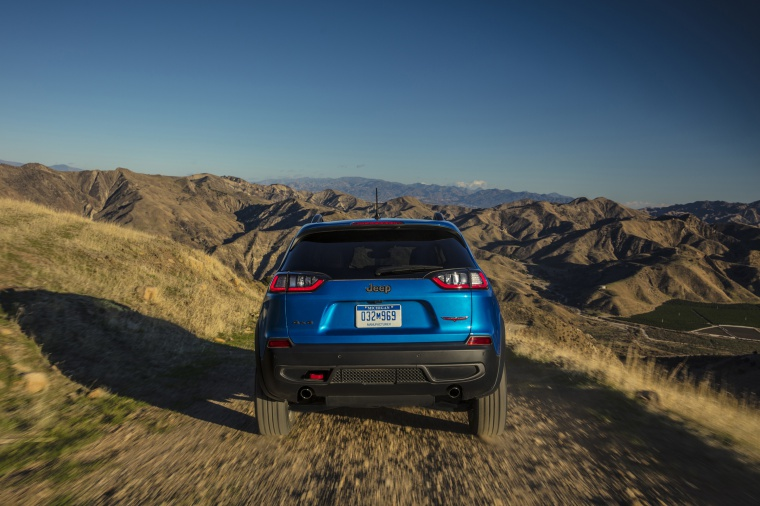 Picture of a driving 2020 Jeep Cherokee Trailhawk 4WD in Hydro Blue Pearlcoat from a rear perspective