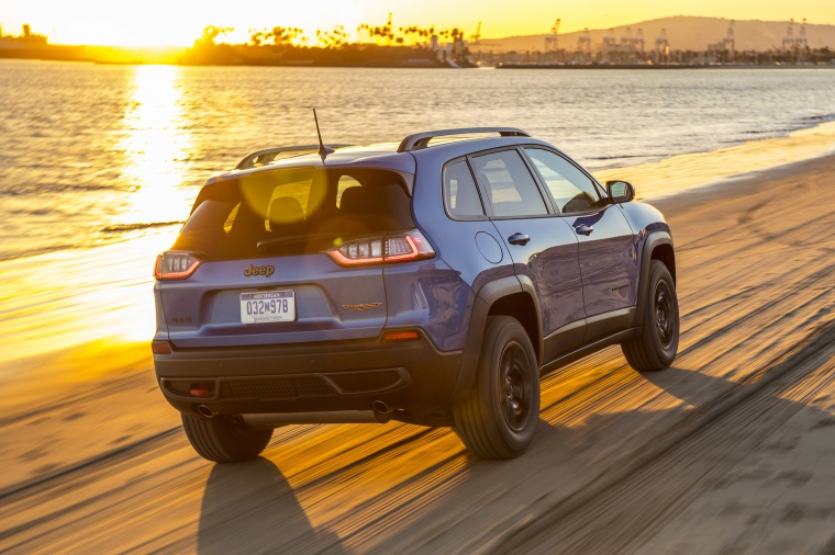 Picture of a driving 2020 Jeep Cherokee Trailhawk 4WD in Hydro Blue Pearlcoat from a rear right three-quarter perspective