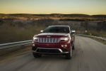 Picture of a driving 2016 Jeep Grand Cherokee Summit 4WD in Deep Cherry Red Crystal Pearlcoat from a front left perspective