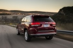 Picture of a driving 2016 Jeep Grand Cherokee Summit 4WD in Deep Cherry Red Crystal Pearlcoat from a rear left perspective