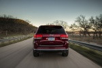 Picture of a driving 2016 Jeep Grand Cherokee Summit 4WD in Deep Cherry Red Crystal Pearlcoat from a rear perspective