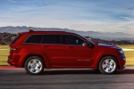 Picture of a driving 2016 Jeep Grand Cherokee SRT 4WD in Redline 2 Coat Pearl from a side perspective