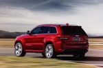 Picture of a driving 2016 Jeep Grand Cherokee SRT 4WD in Redline 2 Coat Pearl from a rear left perspective